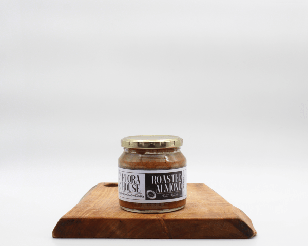 Flora House Almond butter on a wooden board with a white background