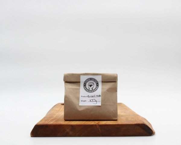 Raw Brazil nuts in a brown biodegradable back sitting on a woden board with a white background