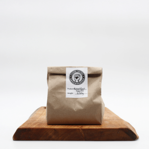 Breakfast Seed mix in a brown biodegradable bag sitting on a wooden board with a white background