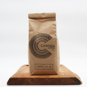 Camissa Darkhouse coffee sitting on a wooden board with a white background