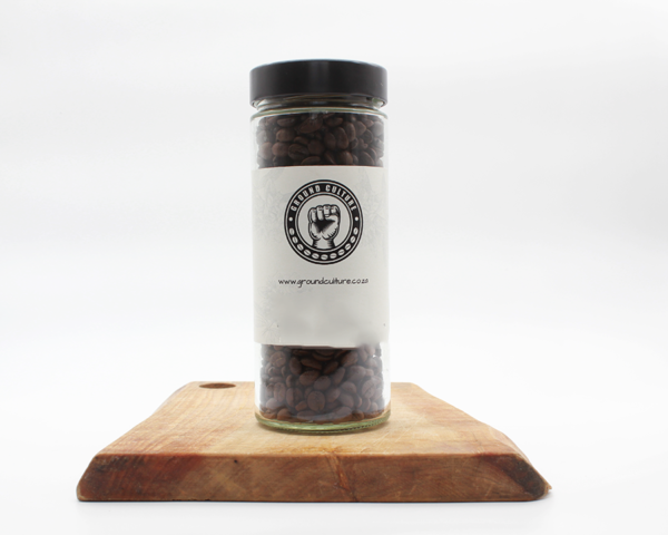 camissa coffee in a glass jar sitting on a wooden board with a white background