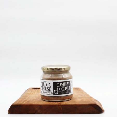 Flora House Coconut cashew roasted butter jar sitting on a wooden board with a white background