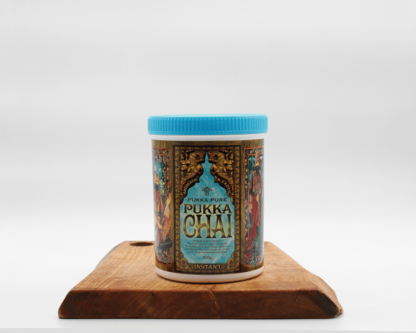 Pukka Pure Chai latte powder in a tub on a wooden board with a white background