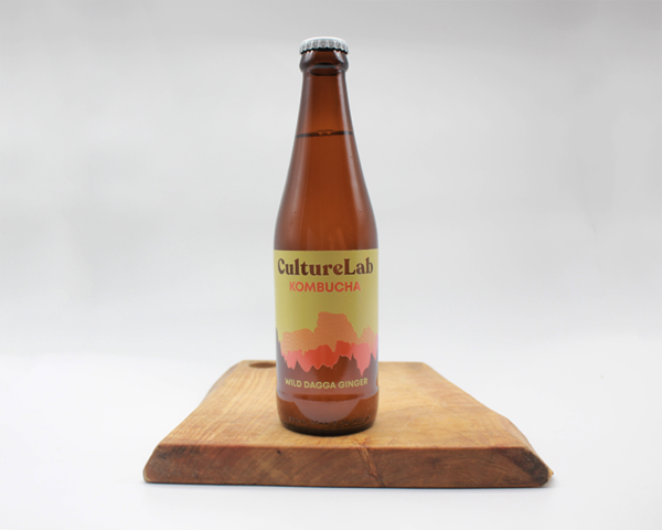 Ginger wild dagga flavoured kombucha by culture lab in a glass bottle sitting on a wooden board with a white background