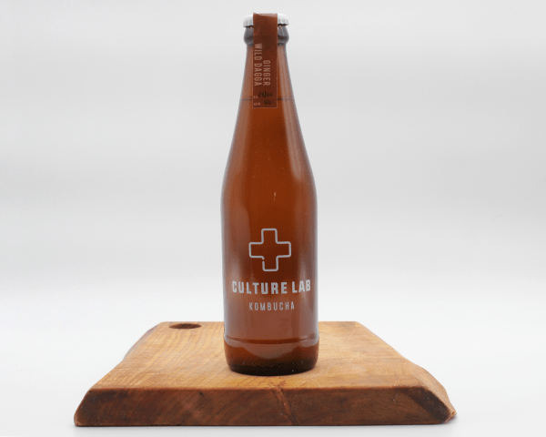 Ginger wild dagga kombucha bottle on a wooden board with a white background