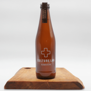Culture Lab Hibiscus Cinnamon kombucha bottle on a wooden board with a white background