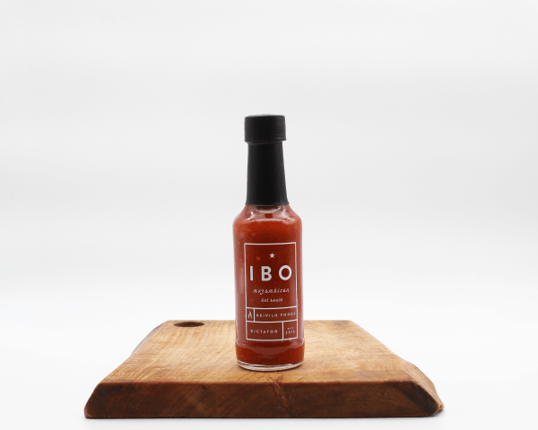 IBO Mozambiquan Hot Sauce on a Wooden board with a white background