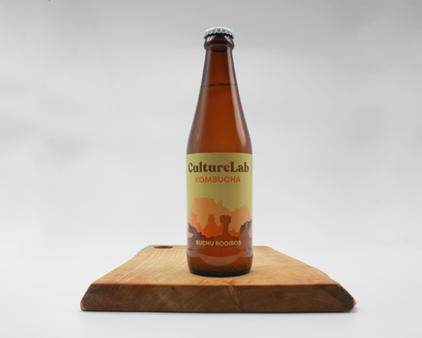 Green buchu kombucha by culture lab in a glass bottle sitting on a wooden board with a white background
