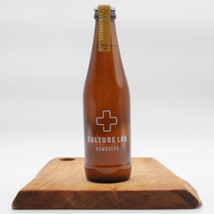 Culture Lab lemongrass kombucha bottle on a wooden board with a white background