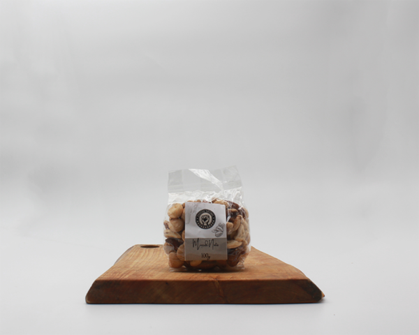 mixed nuts in eco packaging sitting on a wooden board with a white background