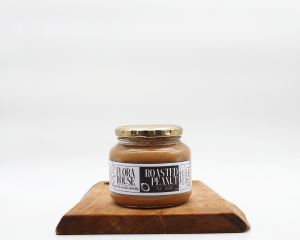 Organic Peanut Butter made by Flora House sitting on a wooden table