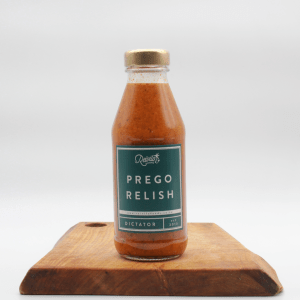 Dictator Prego Relish in a glass bottle on a wooden board with a white background