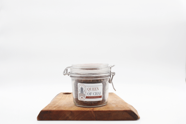 Rooibos Masala Jar sitting on a wooden board with a white background.