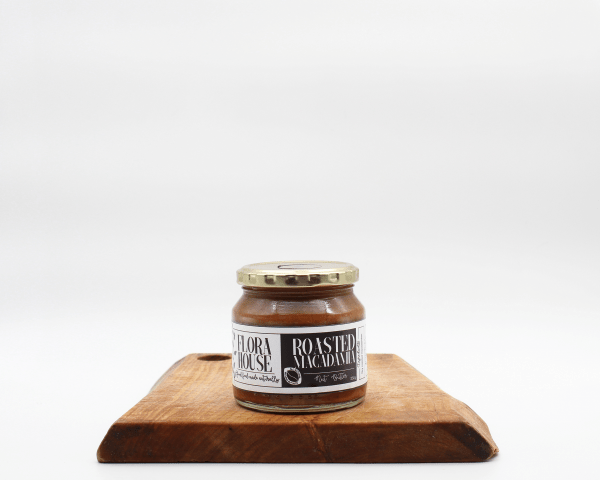 Organic Roasted Macadamia Butter made by Flora House sitting on a wooden board with a white background