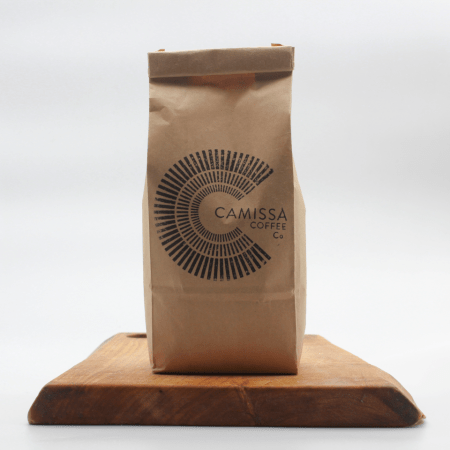 Camissa Ethiopian Coffee in eco packaging on a wooden board with a white background