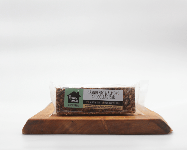 Cranberry & Almond Chocolate bar on a wooden board with a white background