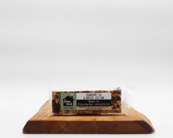 Cranberry,fig and apricot seed bar on a wooden bar with a white background