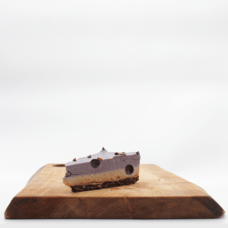Herbivorous blueberry cheesecake slice on a wooden board with a white background