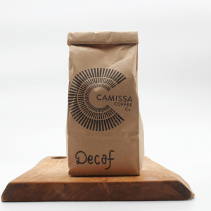 Camissa Mexican decaf sitting on a wooden board with a white background