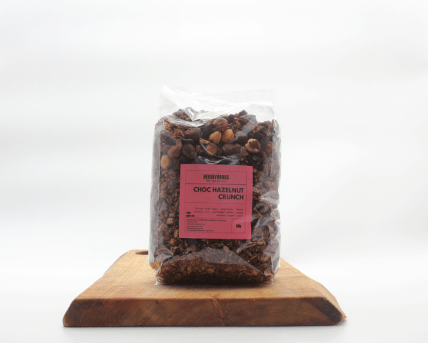 Choc Hazelnut Granola sitting on a wooden board with a white background.