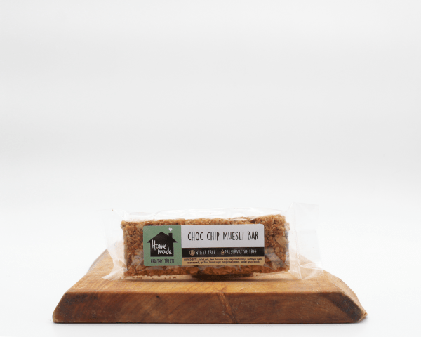 Choc chip muesli bar sitting on a wooden bar with a white background.