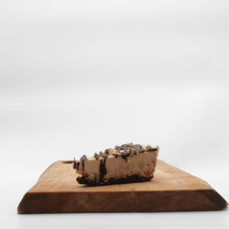 Cookies n Cream Cheesecake slice on a wooden board with a white background.