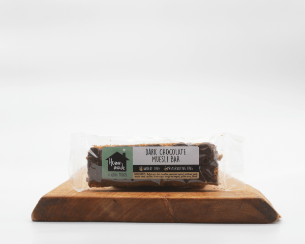 dark chocolate muesli bar on a wooden board with white background