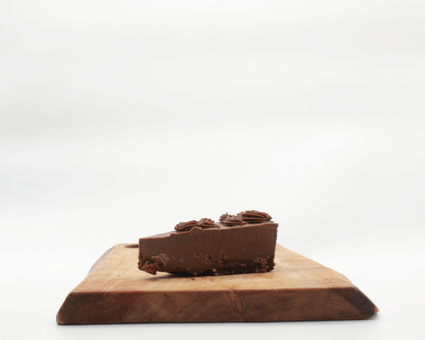 Death by Chocolate Cheesecake slice by Herbivorous sitting on a wooden board with a white background