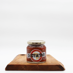 Dictator Chili relish jar sitting on a wooden board with a white background
