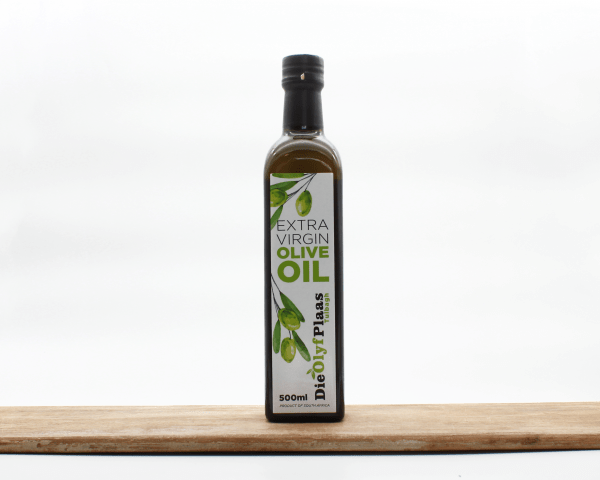 Die Olyf Plaas olive oil in a bottle on a wooden board with a white background