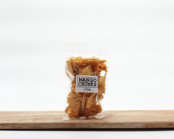 Dried Mango chunks in cornstarch packaging on a wooden board with a white background
