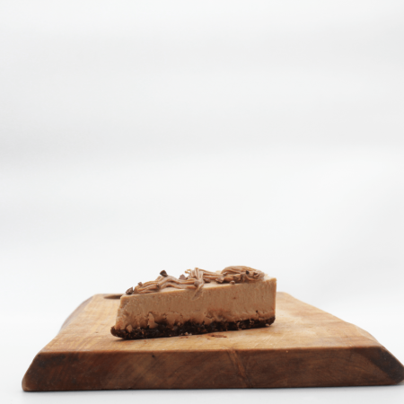 Herbivorous Salted Caramel Cheesecake slice on a wooden board with a white background