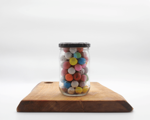 Speckled Eggs in a jar sitting on a wooden board with a white background