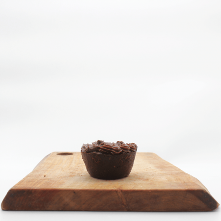 Herbivorous Unbaked Choc Cupcake sitting on a wooden board with white background