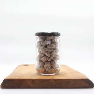 Yogurt Peanuts in a glass jar sitting on a wooden board with a white backgr