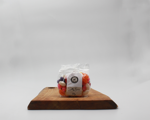 jelly beqans in eco packaging sitting on a wooden board with a white background