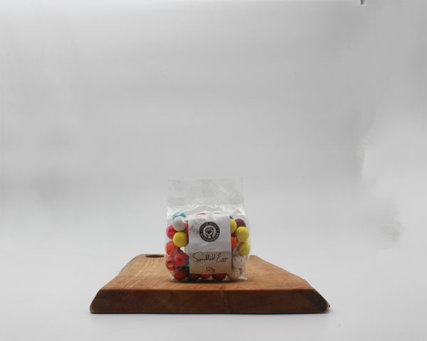 speckled eggs in eco friendly packaging sitting on a wooden board with a white background