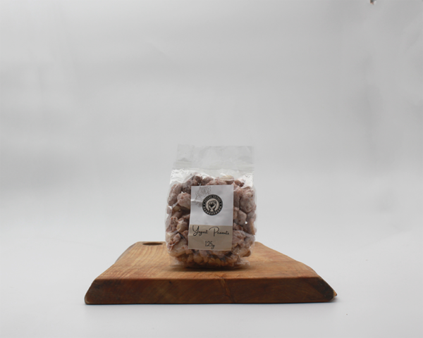 yogurt coated peanuts in eco packaging sitting on a wooden board with a white background