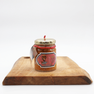 Pili Pili Hot Chili Sauce jar sitting on a wooden board with a white background