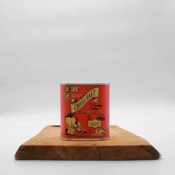 Smoking Hot chilli salt in a tin on a wooden board with a white background.