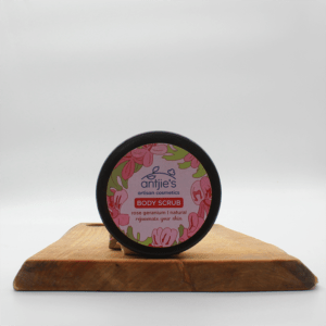 Rose geranium body scrub in a container sitting on a wooden board with a white background