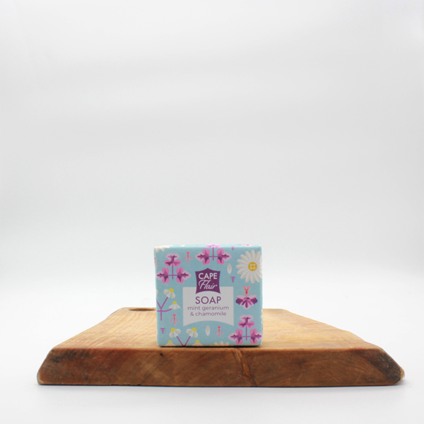 Mint,geranium and chamomile natural soap from the Western Cape in paper wrapping sitting on a wooden board with a white background