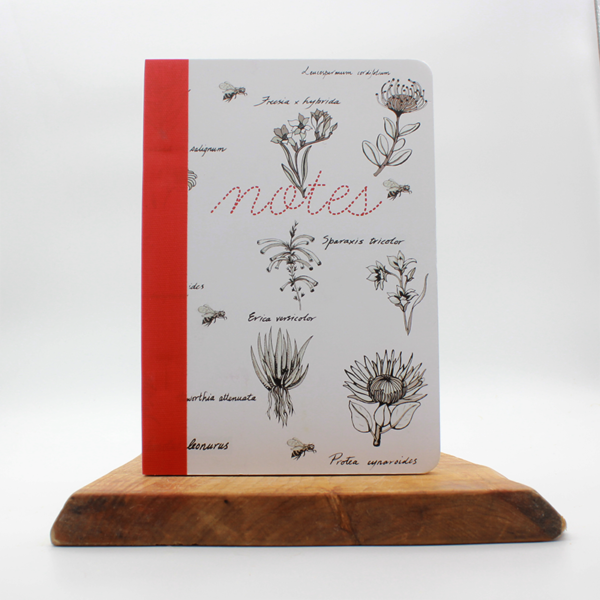 south african fynbos notebook sitting on a wooden board with a white background