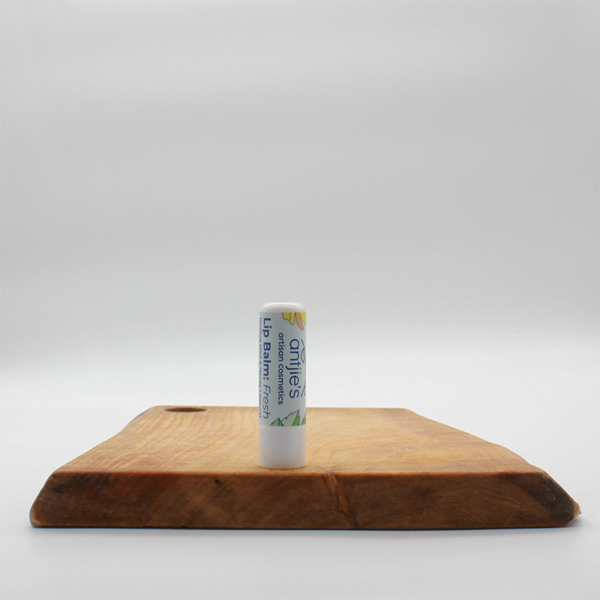 natural Mint & Honey Lipbalms tube sitting on a wooden board with a white background
