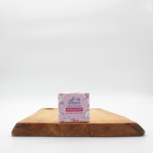 lavender and goat milk natural soap in paper packaging sitting on a wooden board with a white background