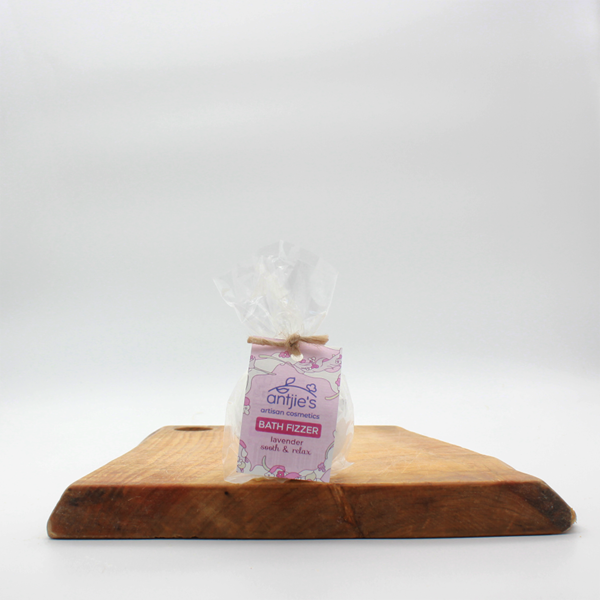 natural lavender bath fizzer sitting on a wooden board with a white background