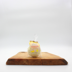 natural mustard bath fizzer in bioplastic packaging sitting on a wooden board with a white background.