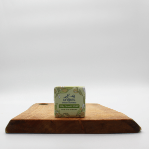 Olive oil and lavender soap sitting on a wooden board with a white background.