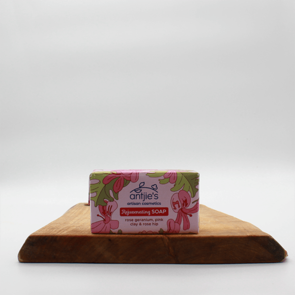 rose geranium soap in pink packaging sitting on a wooden board with a white background.