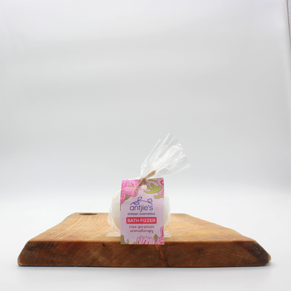 natural rose geranium bath fizzer in bioplastic packaging sitting on a wooden board with a white background